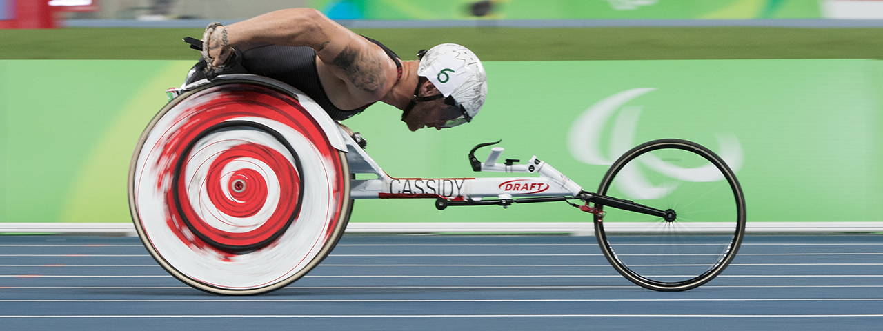 Josh Cassidy is wheelchair racing in his lane, his wheel stands out as it rotates through red, black and white